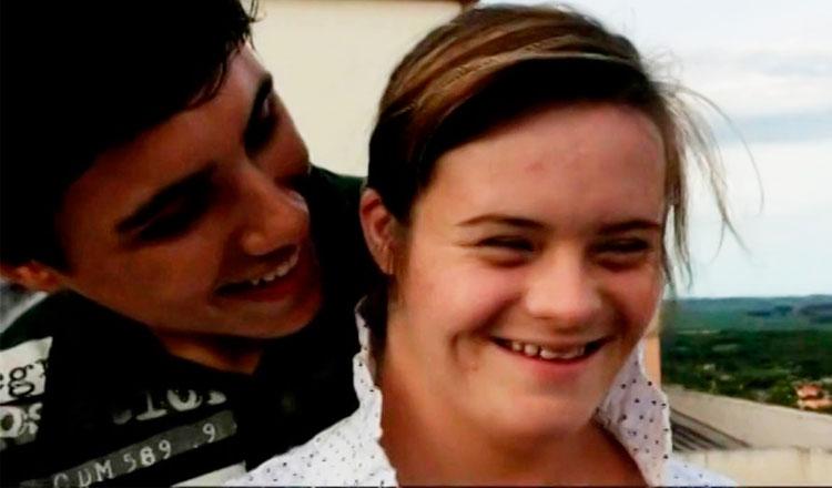Rapaz abraça moça por trás e ambos sorriem