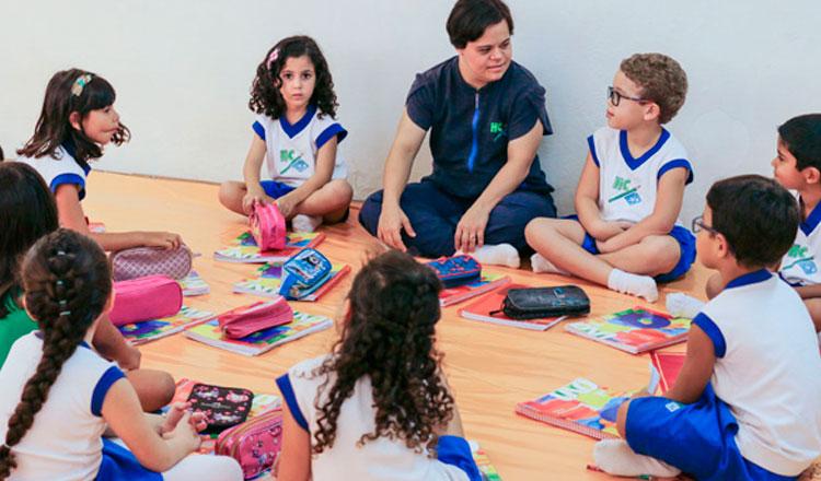 Professora sentada no chão com seus alunos, formando um círculo