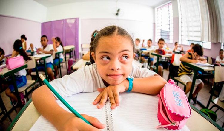 Garota com Síndrome de Down em uma sala de aula, escrevendo a lápis em um caderno