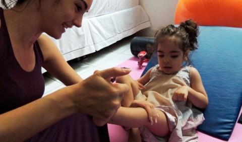 Moça faz exercício na perna de uma garotinha deitada sobre almofadas. Ao fundo, uma bola laranja grande e um sofá branco