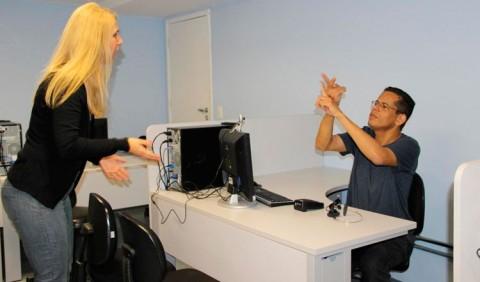 Mulher em pé e homem sentado conversam na Linguagem de Sinais em um escritório