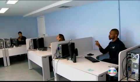 Grande sala, com dois homens e uma mulher em computadores