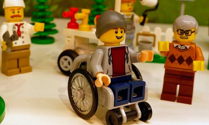 Quatro bonequinhos da Lego, um deles em cadeira de rodas
