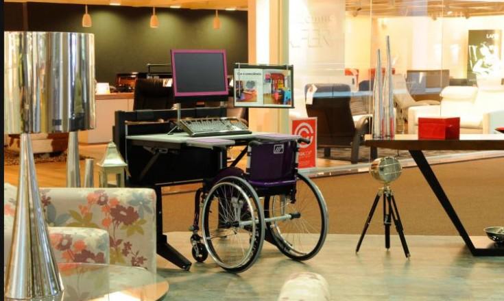 Uma sala com uma cadeira de rodas ao centro e em frente a uma mesa na altura adequada