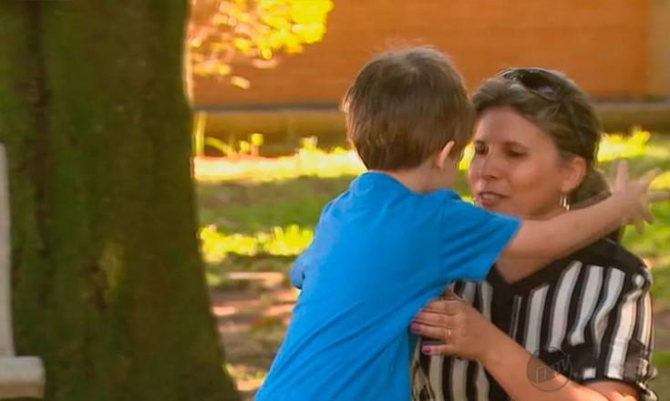 Mulher ajoelhada abraça um garotinho em um parque