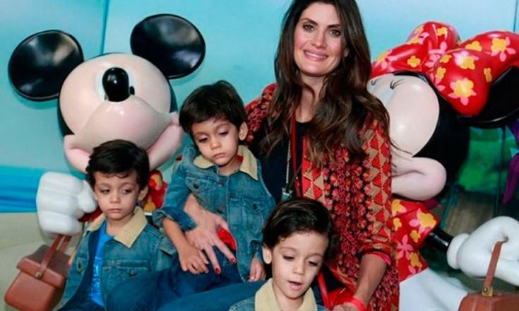 Mulher ao centro cercada de três garotinhos em um cenário do Mickey e da Minnie