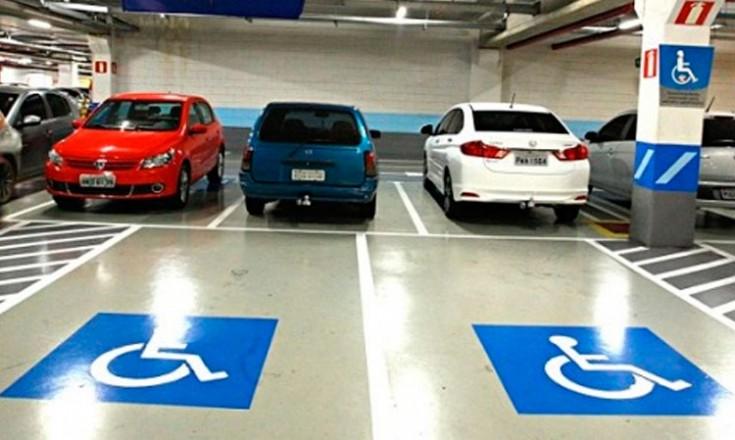 Estacionamento com duas vagas marcadas com o selo de pessoas com deficientes pintada no chão