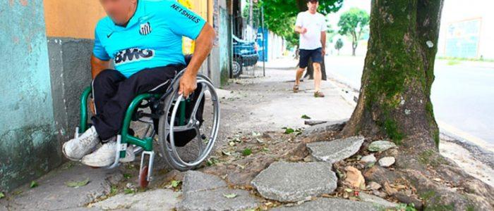 Cadeirante tentando passar em uma calçada quebrada