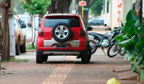 Carro parado em cima de uma calçada, impedindo a passagem de pedestres