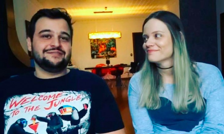 Um homem e uma mulher em primeiro plano, ela olhando pra ele, e uma mesa com um quadro em segundo plano