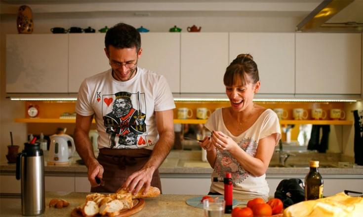 Homem e mulher na cozinha, preparando uma comida
