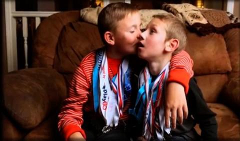 Dois garotos em um sofá marrom. Um deles, à esquerda, está com o braço no ombro do outro e beijando sua bochecha