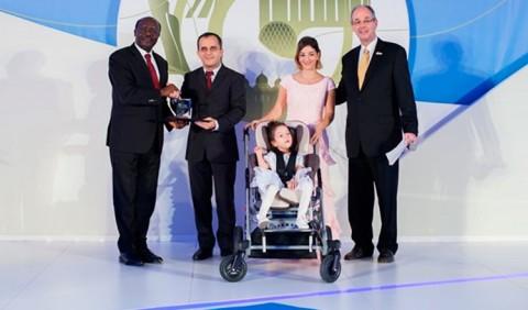 Cinco pessoas posam de frente: um homem negro à esquerda entrega um objeto a outro homem. Ao lado, uma mulher com um terceiro homem ao seu lado, segurando um carrinho com uma criança sentada nele