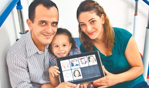 Três pessoas sentadas em uma esteira de exercícios físicos: um homem à esquerda, uma garotinha ao centro e uma mulher à direita, segurando um tablet