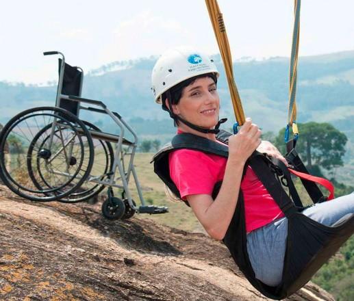 Moça de capacete em um suporte de rapel e, no plano de fundo, uma cadeira de rodas