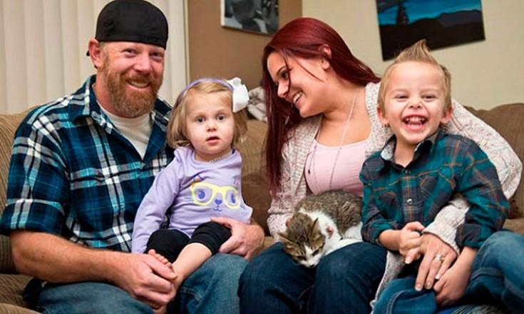 Quatro pessoas sentadas em um sofá, sendo o pai com uma garotinha no colo, e a mãe com um garotinho e uma gata no seu colo