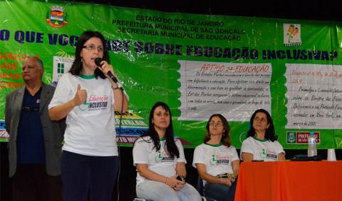 Mulher em pé fala ao microfone ao lado de três outras, sentadas. Atrás delas, um painel verde