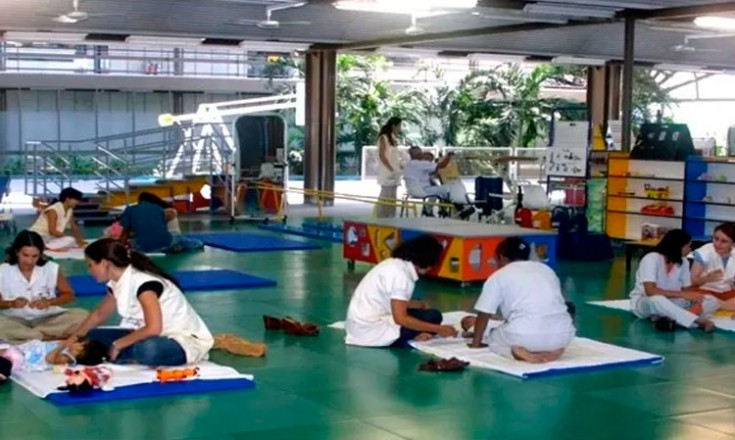 Um grande salão com várias profissionais de saúde realizando atividades de reabilitação em bebês com microcefalia