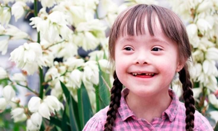 Garotinha com Síndrome de Down sorrindo em frente a um jardim