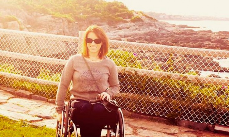 Mulher em uma cadeira de rodas de frente para o mar