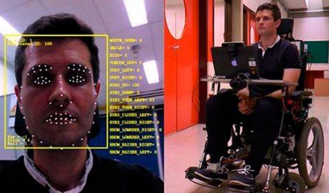Duas fotos, lado a lado; à esquerda, um rosto masculino com vários pontos em torno dos olhos, boca e nariz e uma marcação, em amarelo, de computador; à direita, o mesmo homem em uma cadeira de rodas controlada por movimentos faciais