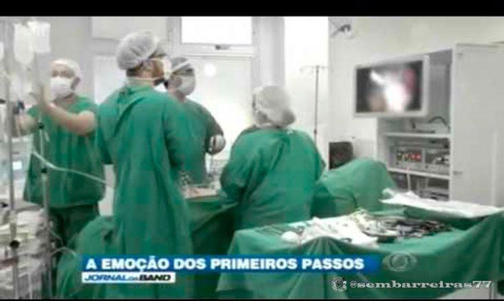 Centro cirúrgico com quatro médicos usando jalecos verdes, tocas e máscaras brancas, preparando-se para iniciar uma cirurgia