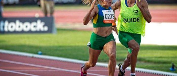 Corredora cega paralímpica durante uma prova ao lado do seu corredor guia.