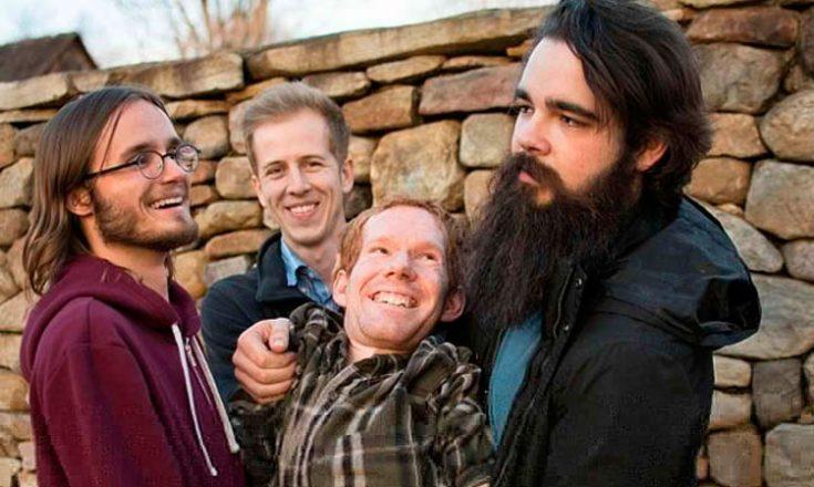 Quatro rapazes sorrindo em frente a um muro de pedras. Um deles, barbado, segura um outro nos braços.