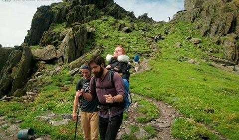 Imagem mostra uma trilha por uma área montanhosa, muito verde. Ao fundo, pessoas seguindo pela trilha. Em destaque, dois rapazes, com um deles carregando uma mochila nas costas e um outro rapaz sentado nela