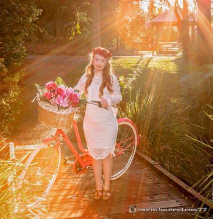 Foto quadrada, em um jardim, com efeito da luz do sol sobre uma jovem em pé ao centro, segurando uma bicicleta. Ela usa um vestido branco até o joelho, uma tiara de flores na cabeça, sandálias e, na cestinha da bicicleta, mais flores.