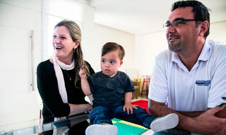 Casal brinca com um garotinho com Síndrome de Down, sentado em uma mesa