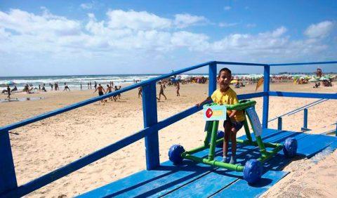 Foto tirada em uma praia em que um garotinho passeia em uma esteira azul com um andador verde feito com tubos de pvc