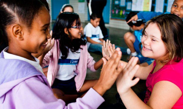 Sala de aula com sete alunos. Em primeiro plano, uma garotinha negra brinca com uma outra, com Síndrome de Down