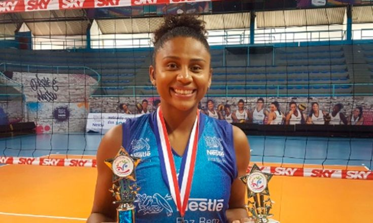 Jogadora negra de vôlei sorri com uma medalha no peito e dois troféus nas mãos. Atrás dela, uma rede de vôlei