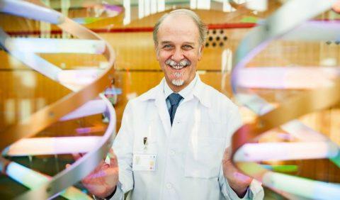 Homem de meia idade, calvo, usando roupa branca, em um laboratório
