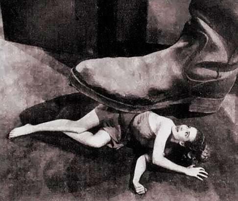 Foto em preto e branco de uma mulher pequena, caída no chão, e um pé enorme a esmagando