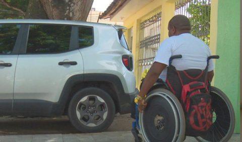 Cadeirante em primeiro plano não consegue atravessar uma calçada, pois há um carro estacionado em cima dela