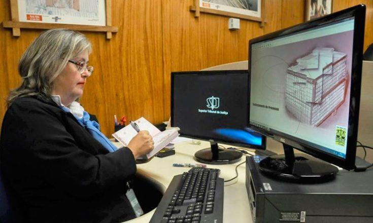 Liane Collares em um de seus empregos, sentada em estação de trabalho, com duas telas de computadora a sua frente, fazendo anotações com caneta em uma agenda.