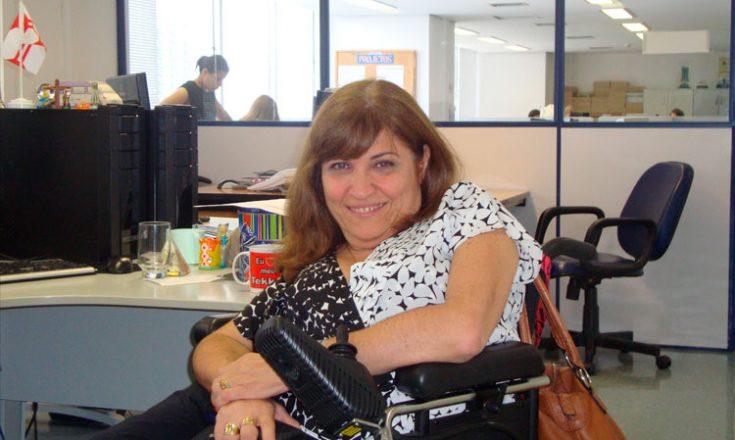 Mulher em cadeira de rodas sorri em um escritório