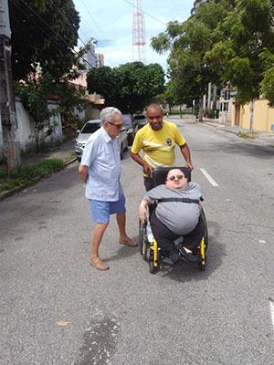 Três pessoas em uma rua: um na cadeira de rodas, um senhor ao seu lado e um terceiro empurrando a cadeira