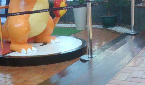 Três batentes em primeiro plano e, ao fundo, uma corda de isolamento com o nome Iguatemi escrito nela e, atrás, a metade da escultura do Pokémon Charizard