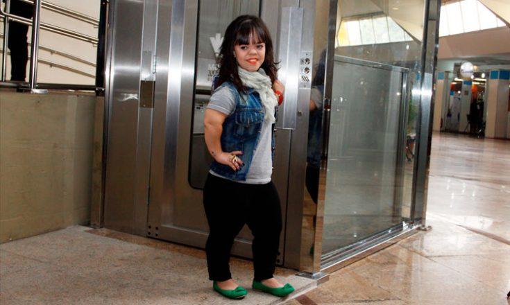 Garota com nanismo posa em frente ao elevador especial