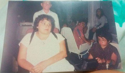 Foto antiga, meio desbotada, mostrando três pessoas em primeiro plano (duas mulheres e um homem) e quatro ao fundo