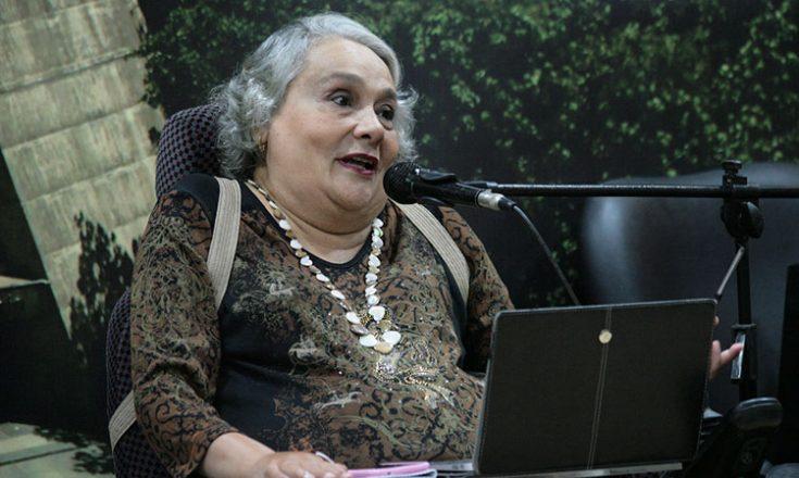 Mulher de meia idade, cabelos brancos, falando ao microfone