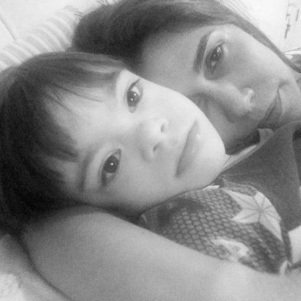 Foto em preto e branco de uma mãe abraçada a seu filho com Síndrome de Down, ambos na cama
