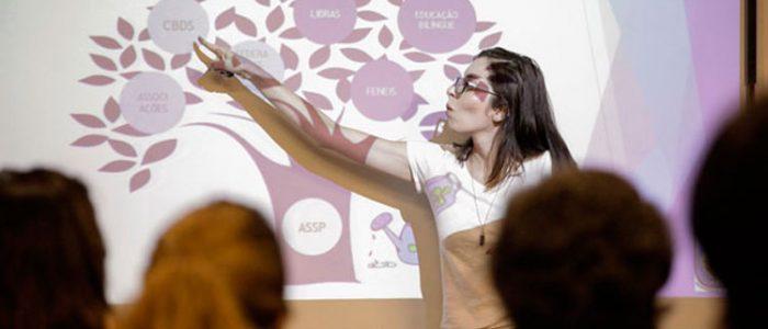 Garota de óculos apontando para um desenho de uma árvore no quadro negro