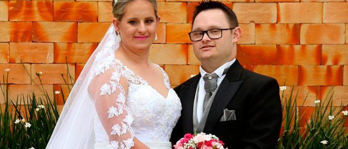 Casal com Síndrome de Down, ela usando vestido branco de noiva e segurando um buquê; ele, de paletó preto, blusa social branca e gravata marfim