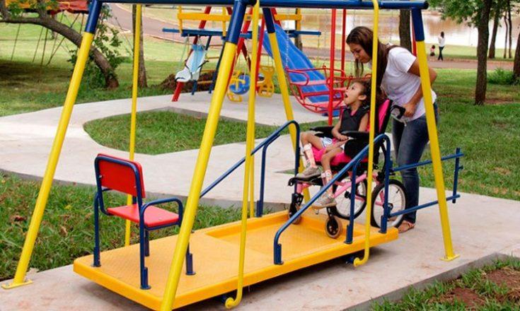 Parque de diversão em que uma garotinha, em uma cadeira de rodas, brinca em um balanço amarelo adaptado, empurrada por uma mulher