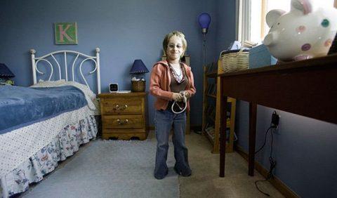 Uma mulher sorrindo, de pé, em um quarto, com uma cama à esquerda, mesa de cabeceira ao fundo e uma estante à direita