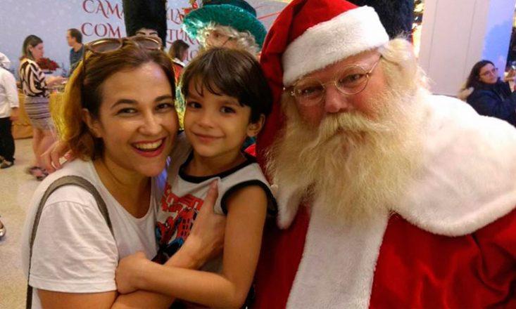 Foto de frente com três pessoas: à esquerda, uma mulher sorrindo, com um garotinho no colo, e papai noel à direita. Ao fundo, várias pessoas passeando em um shopping center